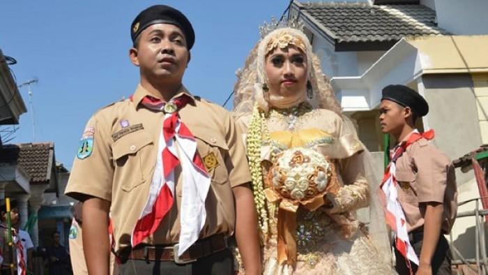 Miftakhurrohman dan Ratih Dwi Septiani Putri Jayanti memilih menikah memakai seragam Pramuka. Bahkan, pelaminannya pun didekorasi menggunakan gubuk dan pionering.